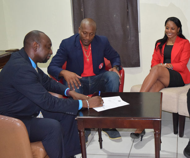 Director of SVGCC Nigel Scott signs the MoU while WIPA Vice President Nixon McLean and Merissa Aguilleria looks on