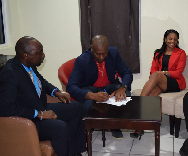 WIPA Vice President Nixon McLean signing the MoU while Director of SVGCC Nigel Scott and WIPA Member Merissa Aguilleria looks on